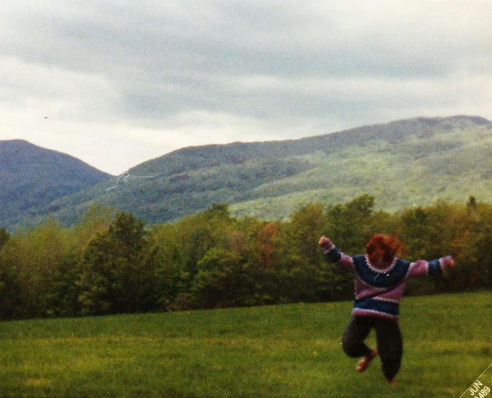 Stacy running through a field in Vermont wearing her favorite striped sweater